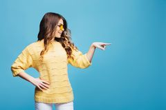 Smiling young lady in yellow sunglasses and sweater pointing finger to the right on the blue background. Smiling young lady in yellow sunglasses and sweater royalty free stock photos