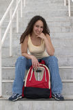 Smiling Young Latina Student with Backpack on stairs. Smiling young Latina student with curly hair holding a red backpack on stairsway Royalty Free Stock Photos