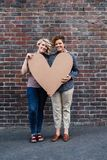 Smiling young lesbian couple holding a heart together outside Stock Photography