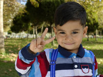 Smiling young little boy gives a Victory Sign Stock Photo