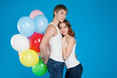 Smiling young love couple holding diversicolored balloons Royalty Free Stock Photo