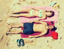 Smiling young lovers sunbathing at sandy beach. In honeymoon stock photography