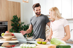 Smiling young loving couple cooking together using laptop Royalty Free Stock Images