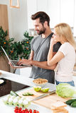 Smiling young loving couple cooking together using laptop Stock Photo
