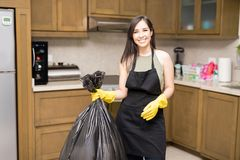 Happy young housewife holding disposal bag with trash. Smiling young maid wearing black apron and yellow latex rubber gloves standing in kitchen holding black Stock Photography