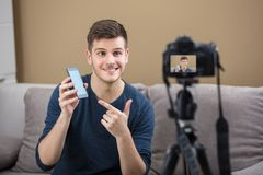 Blogger Holding Mobile Phone Recording Video With Camera. Smiling Young Male Blogger Holding Mobile Phone Recording Video With Camera At Home stock images