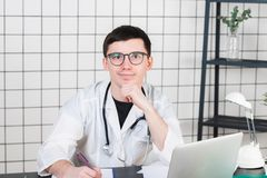 Smiling young male doctor working at the clinic reception, he is using a computer and writing medical reports royalty free stock photos
