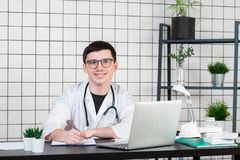 Smiling young male doctor working at the clinic reception, he is using a computer and writing medical reports royalty free stock images