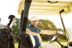 Smiling young male golfer sitting in a golf cart stock photos