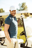 Smiling young male golfer standing at the golf cart Royalty Free Stock Photos