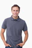 Smiling young male with hands in his pockets. Against a white background Royalty Free Stock Image