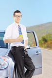 Smiling young male on his automobile holding a coffee cup on a r. Smiling young male on his automobile holding a coffee cup on an open road Stock Image