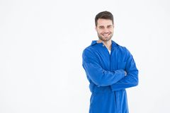 Smiling young male machanic standing arms crossed. Portrait of smiling young male machanic standing arms crossed on white background Stock Images