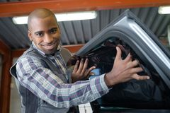 Smiling young male mechanic inspecting car in auto repair. Smiling young male mechanic inspecting a car in auto repair Royalty Free Stock Photography