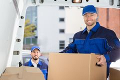 Mover Unloading Cardboard Box From Truck. Smiling Young Male Mover Unloading Cardboard Box From Truck royalty free stock image
