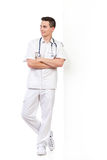 Smiling young male nurse lean on the wall Royalty Free Stock Photography