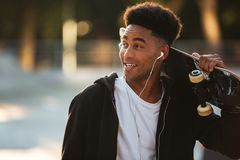 Smiling young male teenager guy with earphones. Holding skateboard on shoulders and looking away outdoors Royalty Free Stock Images