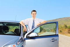 Smiling young male with tie posing next to his car on an open ro Royalty Free Stock Photos