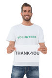 Smiling young male volunteer holding 'thank you' paper Royalty Free Stock Photography