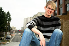 Smiling young man. A smiling young man with a striped pullover sweater and blue jeans Stock Photos