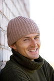 Smiling young man. In a cap and green sweater on a background of a brick wall Royalty Free Stock Image