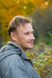 Smiling young man. The smiling young man in a grey jacket against the autumn nature Royalty Free Stock Photo