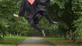 Smiling young man in academic dress walking and jumping, way to future success