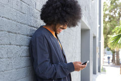 Smiling young man with afro using cell phone Royalty Free Stock Images