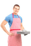Smiling young man in an apron holding a baking tray Stock Photo