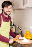 Smiling young man with apron holding a rolling pin Royalty Free Stock Images