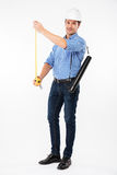 Smiling young man architect in hard hat using measuring tape Royalty Free Stock Photo