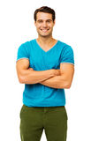 Smiling Young Man With Arms Crossed. Portrait of smiling young man with arms crossed over white background. Vertical shot Royalty Free Stock Images