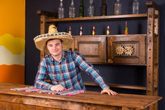 Smiling young man as bartender in a sombrero leaned on bar count. Er in Mexican pub, a shelf with spicy sauces and empty bottles in the background royalty free stock photo