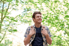 Smiling young man with backpack hiking in woods Stock Photography