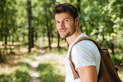 Smiling young man with backpack walking in forest Stock Photo