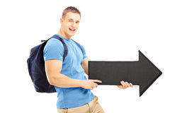 Smiling young man with a bag holding a black big arrow pointing Stock Photos