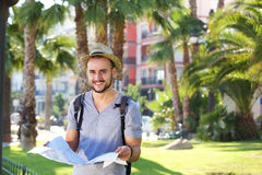 Smiling young man with bag on vacation holding map Royalty Free Stock Photography