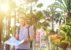 Smiling young man with bag on vacation. Smiling young man with bag standing outside and reading a map Stock Photography