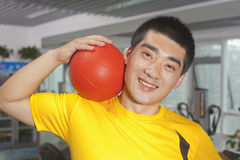 Smiling young man with ball on his shoulder in the gym Royalty Free Stock Photo