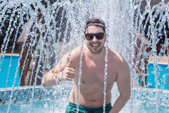 Smiling young man  bathes in pool under water splashes, under fountain. Young man having fun under the fountain water splashes Royalty Free Stock Photo