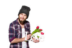 Smiling young man with a beard with decorative word love and red tulips isolated on white background. Smiling young man with a beard wearing in a plaid shirt and Stock Image