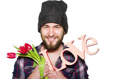 Smiling young man with a beard with decorative word love and red tulips isolated on white background. Smiling young man with a beard wearing in a plaid shirt and Royalty Free Stock Photography