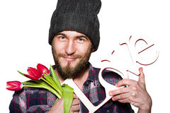 Smiling young man with a beard with decorative word love and red tulips isolated on white background. Smiling young man with a beard wearing in a plaid shirt and Royalty Free Stock Image