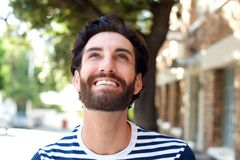 Smiling young man with beard looking up Royalty Free Stock Images