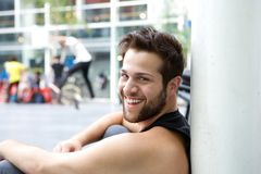 Smiling young man with beard sitting outside. Close up portrait of a smiling young man with beard sitting outside Stock Photo