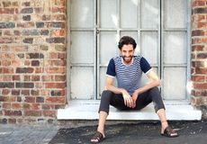 Smiling young man with beard sitting on window sill Stock Photo