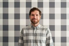 Smiling young man wearing a checkered shirt matching his wallpaper. Smiling young man with a beard standing in front of checkered wallpaper and wearing a stock image