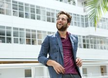 Smiling young man with beard standing in white building Stock Photos