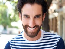Smiling young man with beard and striped shirt Royalty Free Stock Images
