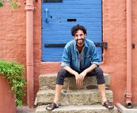 Smiling young man with beard and summer fashion clothes. Portrait of a smiling young man with beard and summer fashion clothes sitting on door step Stock Photography
